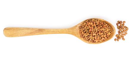 Fenugreek seeds in wooden spoon isolated on white background top view Zdjęcie Seryjne