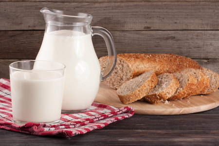 Jug and glass of milk with a loaf of bread on a wooden