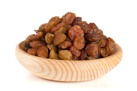 Raisins in a wooden bowl isolated on white