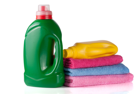 Bottle laundry detergent and conditioner or fabric softener with towels isolated on white