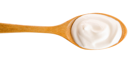Sour cream in wooden spoon isolated on white background. Top view. Flat lay