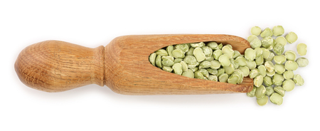 Green split peas in a wooden scoop isolated on white background. Top view