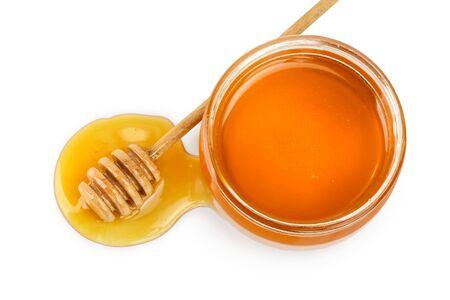 Frasco de vidrio lleno de miel y palo aislado sobre fondo blanco. Foto de archivo
