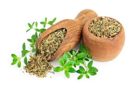 Dried thyme leaves in the wooden bowl and scoop, with fresh thyme isolated on white background. Top view.