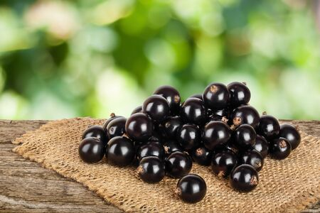 Black currants on burlap and wooden background Stok Fotoğraf - 129831186