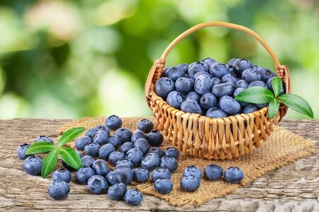 fresh ripe blueberry in wooden basket on table and white background 스톡 콘텐츠
