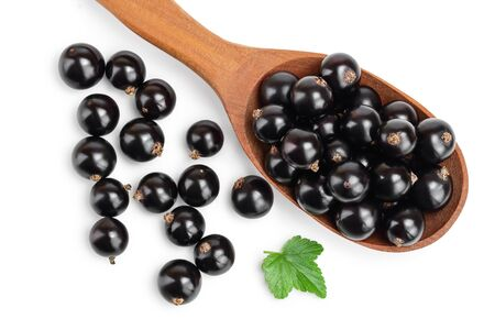 Black currants in spoon on white background.Top view. Flat lay pattern