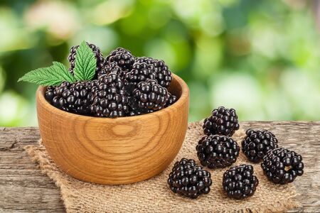 blackberry in bowl on the wooden table with leaf isolated on a white background closeup Stockfoto