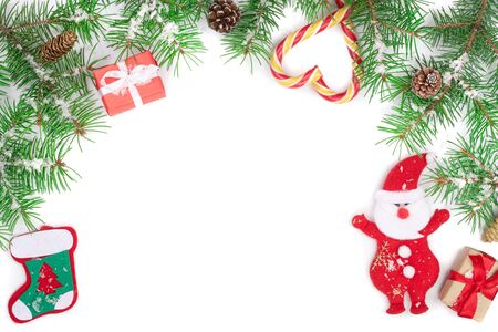 Christmas Frame of Fir tree branch with candy canes and Santa isolated on white background with copy space for your text