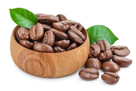 Heap of roasted coffee beans in wooden bowl with leaves isolated on white background