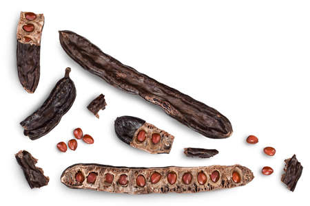 Ripe carob pods and bean isolated on white background with clipping path. Top view with copy space for your text. Flat lay