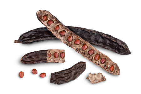 Ripe carob pods and bean isolated on white background with clipping path and full depth of field. Top view. Flat lay