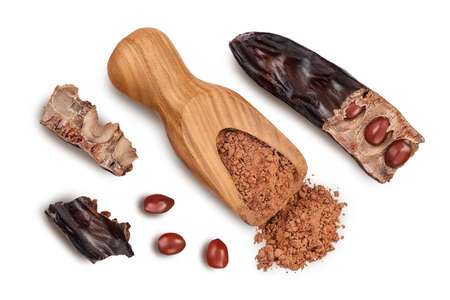Carob pod and powder in wooden scoop isolated on white background with clipping path. Top view. Flat lay