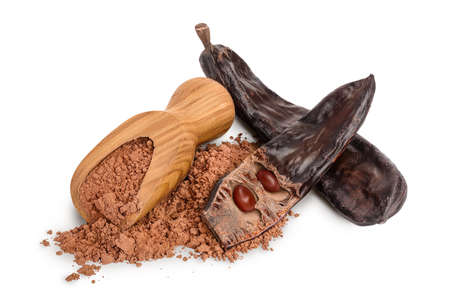Carob pod and powder in wooden scoop isolated on white background with clipping path and full depth of field. 版權商用圖片
