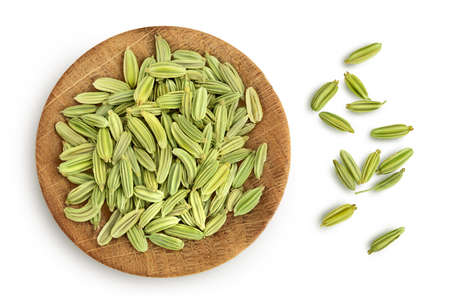 Dried fennel seeds in wooden bowl isolated on white background with  . Top view. Flat lay