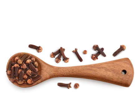 Dry spice cloves in wooden spoon isolated on white background. Top view with copy space for your text. Flat lay