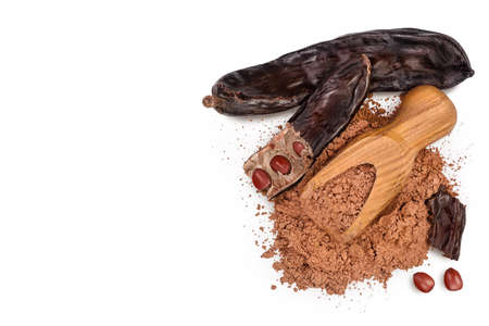 Carob pod and powder in wooden scoop isolated on white background with . Top view with copy space for your text. Flat lay Banque d'images