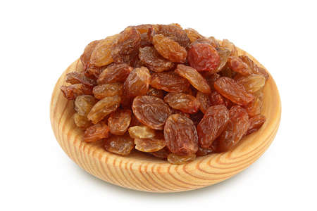 Brown raisins in wooden bowl isolated on white background with path and full depth of field