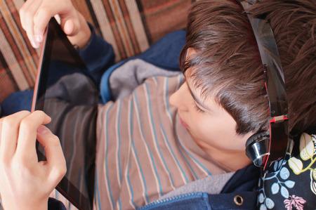 chłopak ze słuchawkami patrzy na tablecie, gadżety