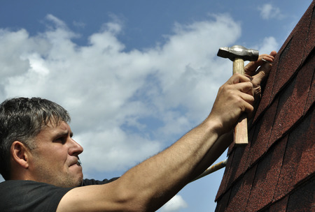 Man with a hammer to drive a nail, roof repairs Zdjęcie Seryjne