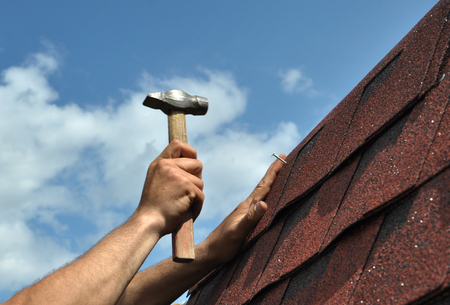 Hand with a hammer to drive a nail, roof repairs Zdjęcie Seryjne