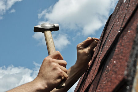 Hand with a hammer to drive a nail, roof repairs Standard-Bild