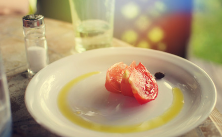 Summer breakfast with piece of tomato, olive oil on a plate Zdjęcie Seryjne