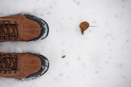 Red boots and dry leaf on the snow