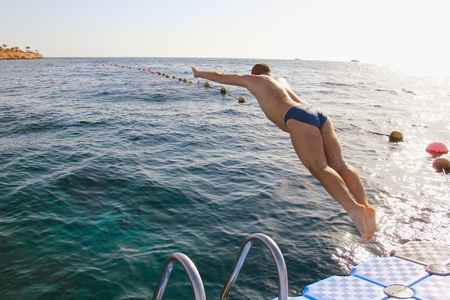 2 persons only: a man jumping from the pontoon bridge into the water, sport leisure, swimming jump into the water soft focus