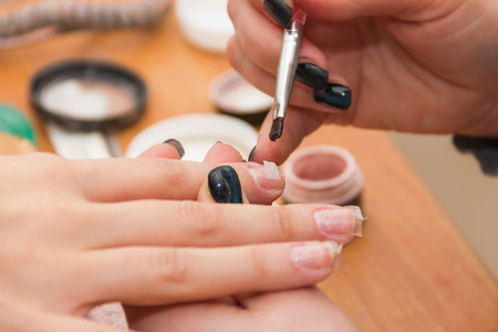 artificial nails: build artificial nails, manicures, artificial nails correction, the industry of beauty and nail care, beauty salons, soft focus Stock Photo