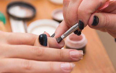 artificial nails: build artificial nails, manicures, artificial nails correction, the industry of beauty and nail care, beauty salons, a process of increasing, in the hands, nail esthetics, soft focus Stock Photo