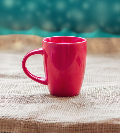 invigorating: Red cup on a table by the window on sackcloth isolated, with a hot drink invigorating Stock Photo