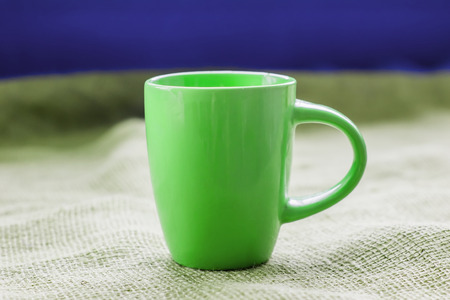 invigorating: green cup on the table by the window on sackcloth isolated, with a hot drink invigorating Stock Photo