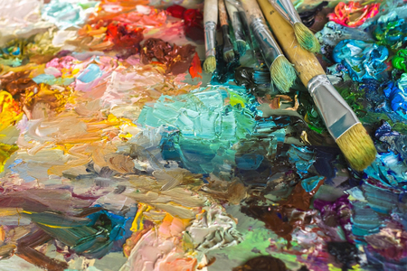 artists palette with oil paints and brushes used for painting and drawing, soft focus Stock Photo
