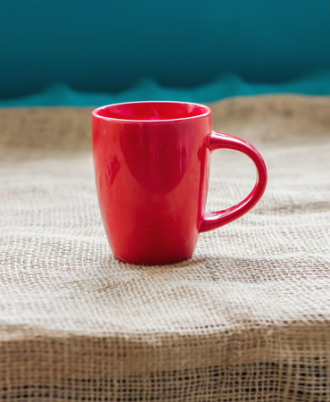 Red cup on a table by the window on sackcloth isolated, with a hot drink invigorating Stock Photo