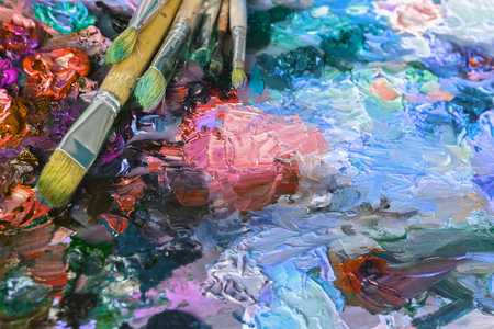 used: artists palette with oil paints and brushes used for painting and drawing, soft focus Stock Photo
