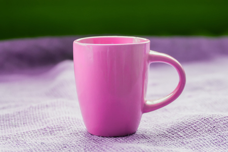 invigorating: pink cup on the table by the window on sackcloth isolated, with a hot drink invigorating Stock Photo