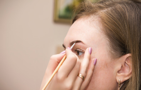 plucking: Correction of eyebrow tweezers, eyebrow henna painting, beautiful young girl beauty salon, plucking and simulation form a perfect eyebrows, tattoos and permanent make-up, soft focus