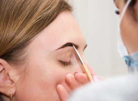 Correction of eyebrow tweezers, eyebrow henna painting, beautiful young girl beauty salon, plucking and simulation form a perfect eyebrows, tattoos and permanent make-up, soft focus