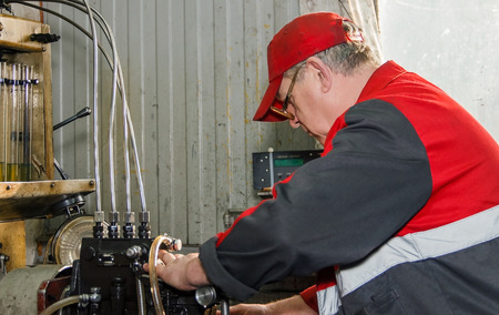 injector: Professional mechanics testing diesel injector in his workshop, repair of diesel fuel injectors, ustroustvo for the diagnosis of fuel injectors soft focus, focus on face