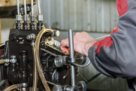 injector: Professional mechanics testing diesel injector in his workshop, repair of diesel fuel injectors, ustroustvo for the diagnosis of fuel injectors
