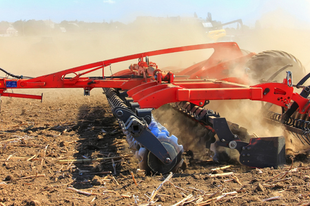Agricultural machinery for the fields. Rattot plow field. The farmer in the tractors is preparing the land for the next season. Cultivated field. The concept of agronomy.
