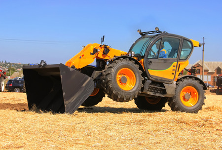 The concept of agronomy, a yellow tractor with a bucket demonstrates work