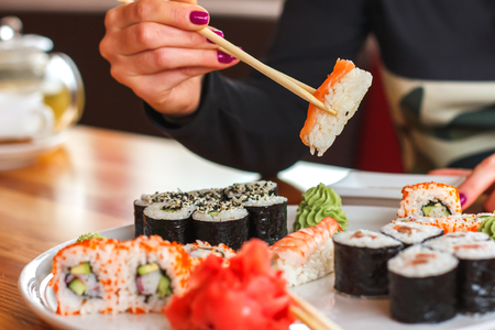 sushi and rolls, Japanese cuisine, a girl eating sushi in a restaurant