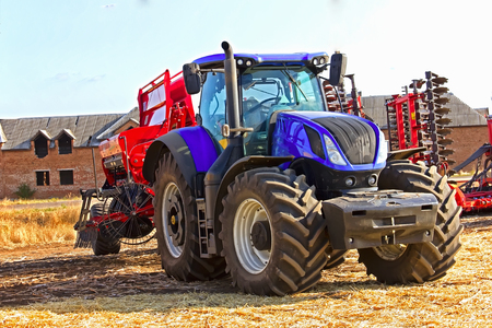 Modern tractor and harvester on the field during a hot harvest Stock Photo