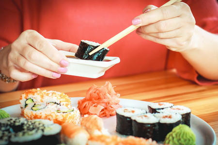 The best sushi rolls, Japanese cuisine. Different delicious kinds of sushi rolls. Cooking. The hand is dipped in soy sauce, delicious food.