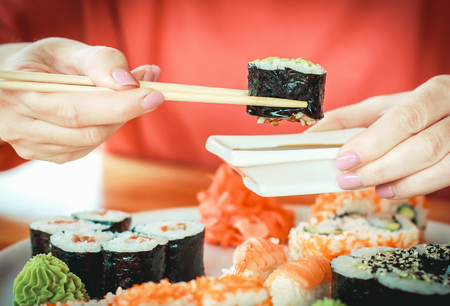 The best sushi rolls, Japanese cuisine. Various delicious sushi rolls. The hand is dipped in soy sauce, delicious food.