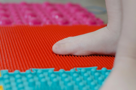 childrens feet on an orthopedic mat