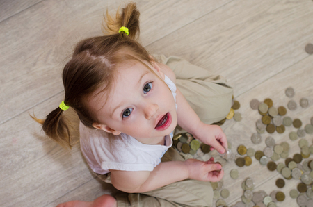little girl counting and playing with coins