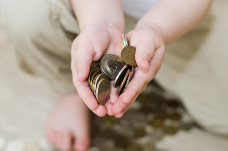 a handful of coins in the hands of a child Banco de Imagens